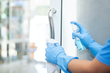 Picture of cleaning professional wearing gloves and spraying disinfectant on office door handle and wiping clean